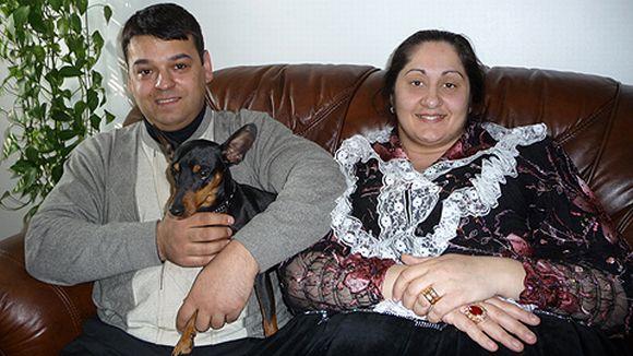 romanimies ja -nainen istuvat sohvalla, miehen sylissä chihuahua-koira