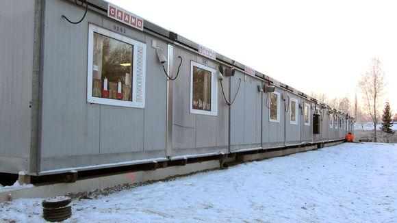 Video: Kuvassa t´rivi harmaita opiskelukäyttöön tarkoitettuja parakeita lumisessa maisemassa, taustalla korjausmiehiä oranseissa asuissa