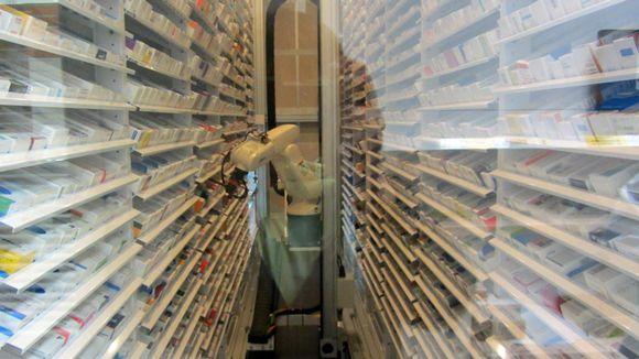 Robotti sijoittaa lääkkeitä hyllyyn apteekissa.