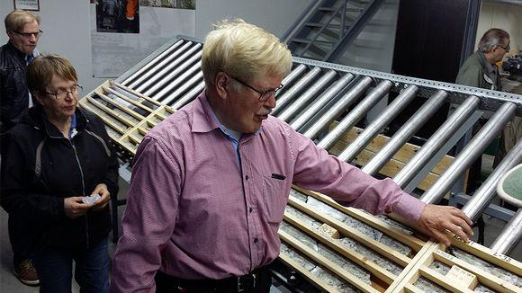 Kuvassa mies esittelee telineillä olevia kairauspötköjä.