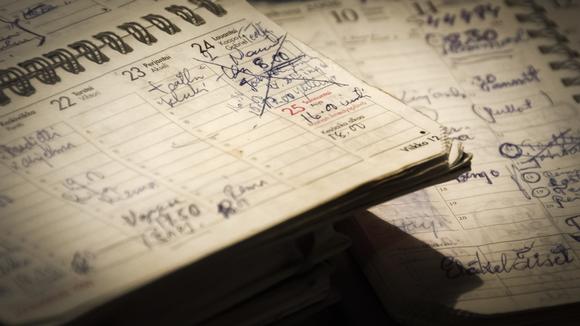 Kierrekantaisia kalentereita pöydällä, kalenterit täynnä merkintöjä.