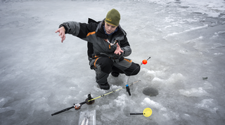 Kalastusopas Markus Sallinen esittelee ismete-kalastusta järven jäällä.