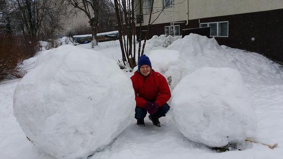 Kuvassa kaksi suurta lumipalloa ja nainen.