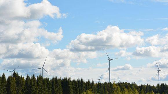 Kuusi tuulivoimalaa peltojen takana metsän yllä .Pajukosken tuulipuisto, Ylivieska