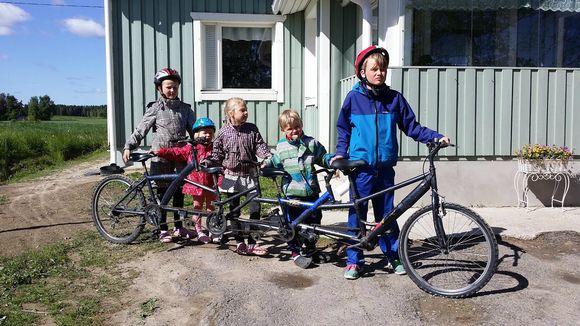 Kuvassa neljä lasta ja pyörä, jossa on neljä paikkaa.