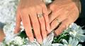 Miehen ja naisen kädet päällekkäin kukkakimpun päällä. Sormissa vihkisormukset.