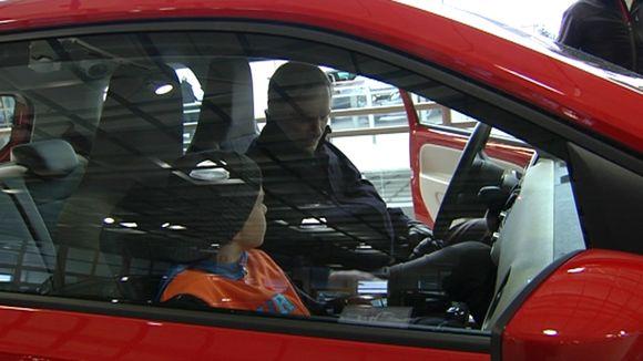 Mies ja poika tutustumassa uuteen autoon.