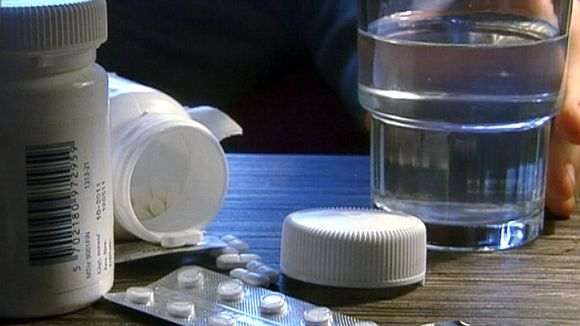 Henkilö tarttumassa vesilasiin ja pillereitä pöydällä.
