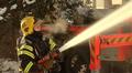 Palomies ruikuttaa vettä palavaan taloon