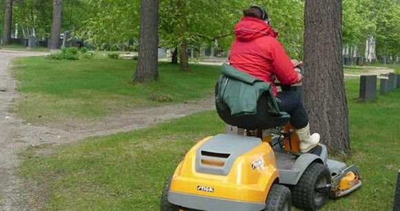 Kesätyöntekijä ajaa ruohoa hautausmaalla.