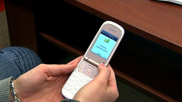 Nainen pitelee kännykkää kädessään. Kännykän ruudulla tekstiviesti.