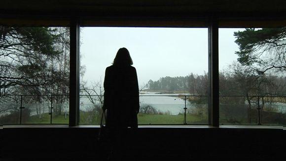 Nainen katsoo ikkunasta avautuvaa merimaisemaa.