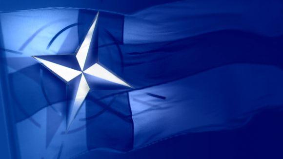Kuva, jossa Naton tunnus edustalla ja Suomen lippu taustalla