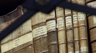 Vanhoja kirkonkirjoja hyllyssä.