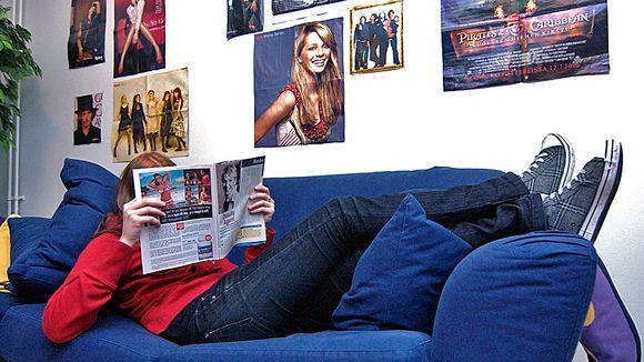 Nuori loikoo sohvalla lukien aikakausilehteä