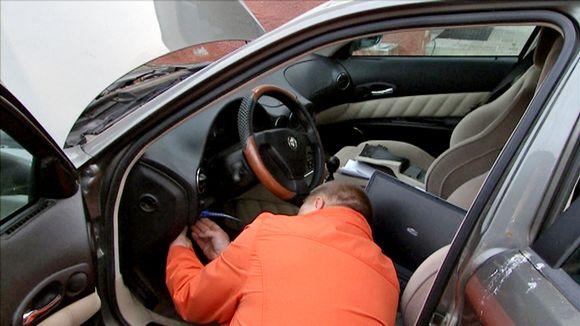 Video: Oranssitakkinen mies säätää auton mittareita. Auton vasemmanpuoleiset ovet ja konepelti ovat auki.