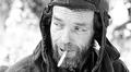 Kasvokuva miehestä metsätöissä talvella. Tupakka suussa.