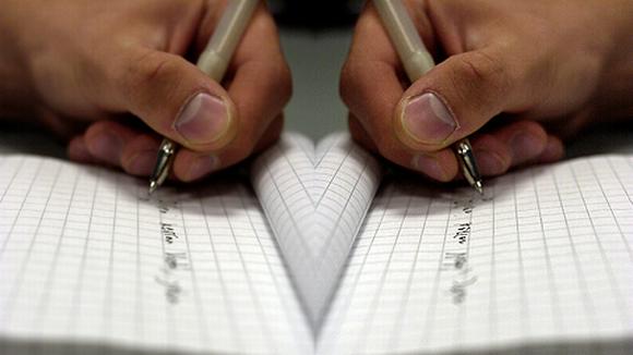 Käsi kirjoittaa paperille, vieressä sama kuva peilikuvana.