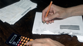 Lyijykynä kädessä, laskin pöydällä. Kirjoittaa avattuun kirjekuoreen numeroita.