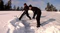 Kaksi miestä kolaa lumimassoja katolta.