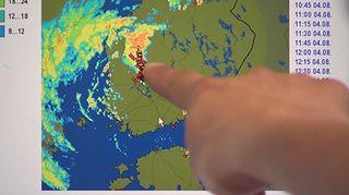 Meteorologi osoittaa tietokonenäytöltä ukkosrintaman liikettä.