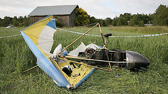 Ultrakevyt pienlentokone makaa pahoin romuttuneena kesäisellä pellolla. Poliisi on ympäröinyt onnettomuuspaikan nauhoilla.