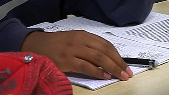 Käsi ja kynä kouluvihkon päällä