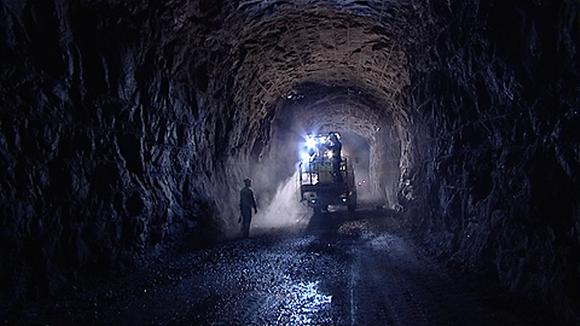 Kiveen louhittu luola. Luolassa kaksi työmiestä valon kajossa.