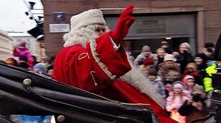 Joulupukki tervehtii kadun varrella olevaa yleisöä.