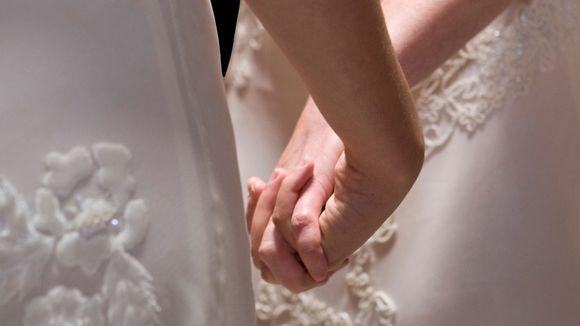 Hääasuiset naiset pitävät toisiaan kädestä.