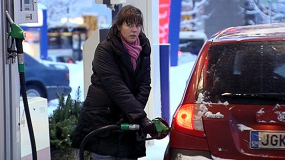 Nainen tankkaa autoa