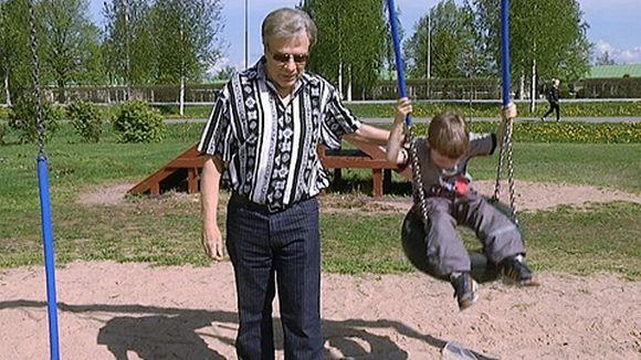 Anton keinumassa isänsä kanssa