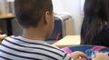 Oppilas istuu pulpetissa koulun luokassa. Kuvattu takaapäin.