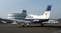 Pienkone lentokentällä, Malmin pyöreä lentoasema lennonjohtotorneineen näkyy taustalla.