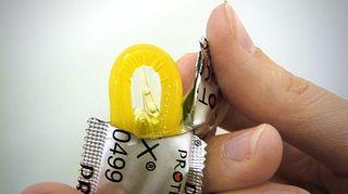 Henkilö avaamassa kondomipakettia.