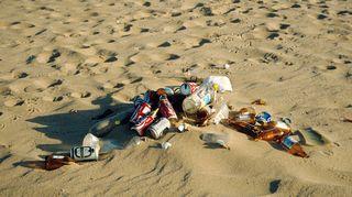 Tyhjiä olut- ja limupulloja rannalla.