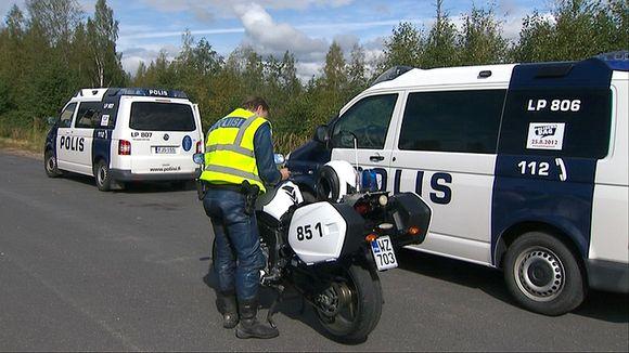 Video: Moottoripyöräpoliisi pyöränsä vierellä ratsiapaikalla.