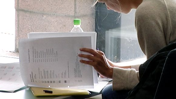 Opiskelija kirjoittaa muistiinpanoja Turun yliopistossa.