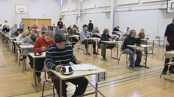 Ylioppilaskirjoitusten osallistujia liikuntasalissa.