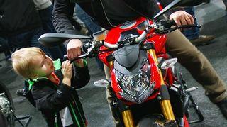 Mies ja poika tutkivat menipeliä moottoripyörämessuilla 2. helmikuuta 2012.