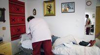 Hoitajat hoitavat vanhusta palvelutalossa.
