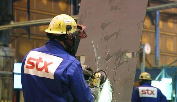 STX:n työntekijä hitsaa telakalla.