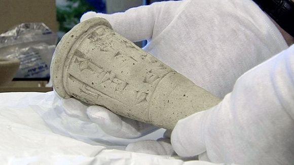 Tutkija pitelee kädessään muinaisesinettä.