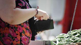 Nainen ostaa herneitä torilla.