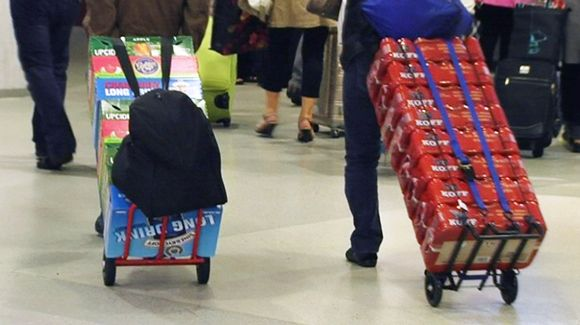 Laatikoittain alkoholia satamaan saapuvien matkustajien kärryissä.