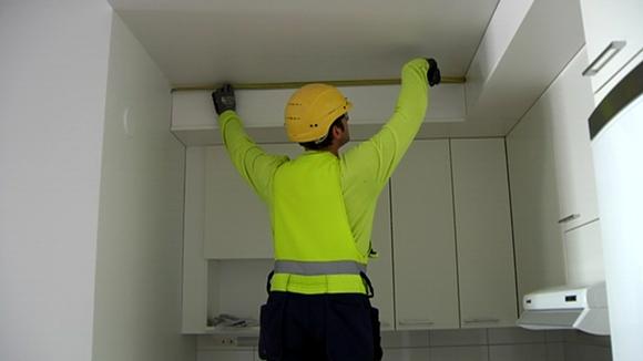 Rakennusmies mittaa listaa.