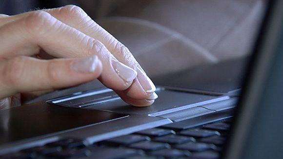 Henkilö käyttämässä kannettavaa tietokonetta.