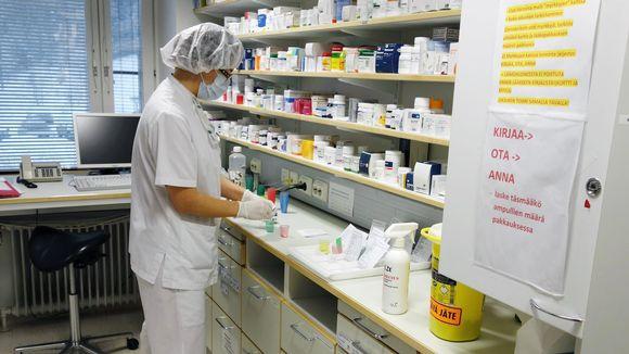 Sairaanhoitaja jakaa lääkkeitä kippoihin.