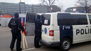 Poliiseja kantamassa lippusalkoja kohti poliisiautoa.