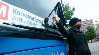 Mielensoittaja seisoo bussin edessä Rautatientorilla.